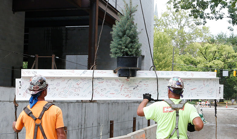 The topping-off beam includes the signatures of 455 students, staff, and faculty